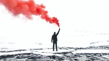 Communication in learning - man sending up a red flare