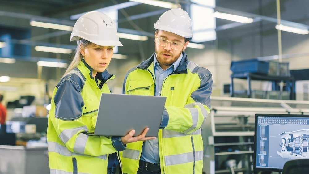 Knowledge sharing on the job - two people in hard hats looking at a laptop screen together